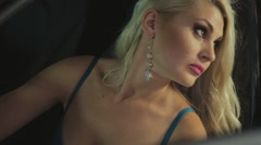 Sexy blonde posing in lingerie next to expensive car in the showroom Stock Footage