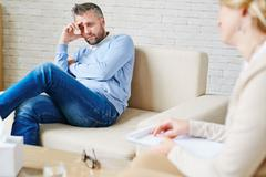 Stressed man sitting on sofa during his visit to psychologist Stock Photos