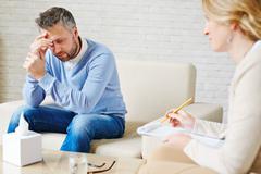 Sad man visiting his psychologist Stock Photos