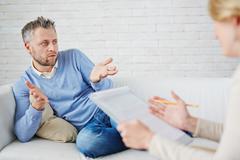 Man describing his problem to psychologist Stock Photos