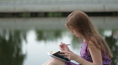 The beautiful young woman write something in her notebook on river bank Stock Footage