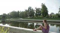 Young girl write something in her notebook on river bank in city park Stock Footage