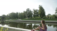 Young woman write something in her notebook on river bank in city park Stock Footage