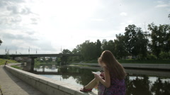 Beautiful woman write something in her notebook on river bank in city park Stock Footage