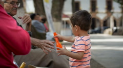 PATZCUARO, MEXICO - CIRCA - An elder helps a boy with a balloon Stock Footage