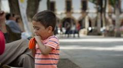 PATZCUARO, MEXICO - CIRCA  - a boy blows up a balloon Stock Footage