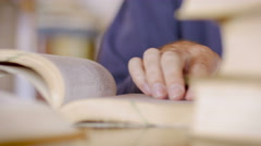 CU of a man's hand scanning a book for information while he reads Stock Footage