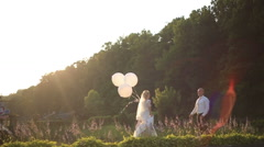 Wedding couple hugging and kissing outdoors in a field with balloons. Bride and Stock Footage