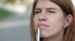 Beautiful young woman face pen handles, against background of summer green park. Stock Footage