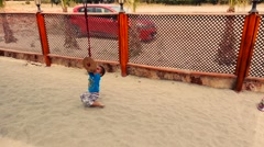 Boy hanging goes down rope-way 2  Stock Footage