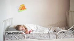 Boy throws a pillow at the girl who sleeps, Happy laughing brother and sister Stock Footage
