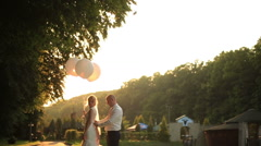 Groom helps bride to adjust her wedding dress in the green park on sunset Stock Footage