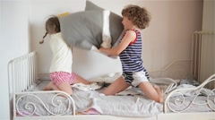 The brother and the sister have arranged fight by pillows on a bed in a bedroom Stock Footage