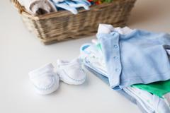 close up of baby clothes for newborn boy in basket - stock photo
