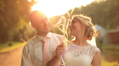 Happy young newlyweds with balloons charmingly smiling on sunset background in Stock Footage