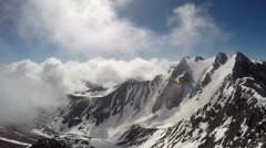 Time lapse of wickedly intense clouds roiling and flowing over peaks Stock Footage
