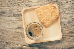 Top view cup of dark hot coffee on wooden table in the morning warm tone Stock Photos