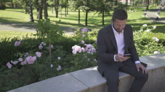 Businessman sitting on wall against park, browsing smartphone. Stock Footage