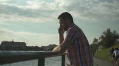 Man calling cell phone by the river near sunset. Stock Footage