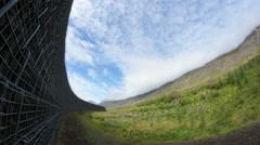 Avalance barrier over Neskaupstadur summer blue sky Iceland fish eye Stock Footage