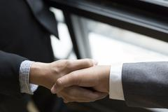 Two businessman in suit shaking hands beside window - business teamwork, coop Stock Photos