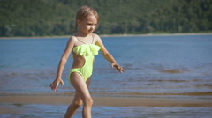 Cute little blonde girl running by a lake with the green mountains on the - stock footage