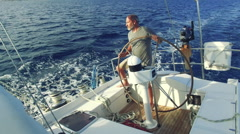 Man is steering his big sailboat on the sea on a sunny day Stock Footage
