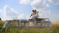 Bride and groom on the top of retro bus in the sunny summer field. Unusual Stock Footage