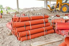 Arranged PVC tubes pipes stacked in rows pattern Stock Photos