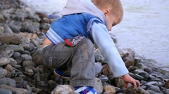 Child throwing stones into the river Stock Footage
