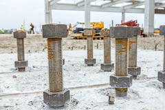 Anchor's nuts on screw are peaking from concrete in new building foundation Stock Photos