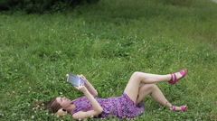 A young woman lying on the grass and reading a book Stock Footage