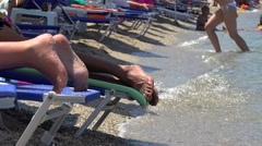Vacationers on sunbeds at a sea beach. Stock Footage