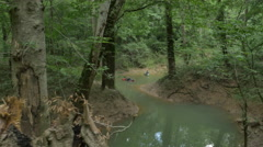 Cinematic Tracking Shot of Kayakers on a Creek in the Forest Stock Footage