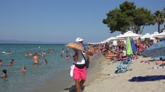 Donuts peddler on the Pefkohori beach with vacationers. Chalcidice, Greece Stock Footage