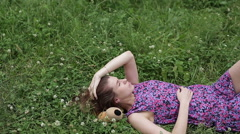Fashion portrait of beautiful sexy female brunette girl model lying on grass in Stock Footage