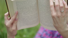 Reading a book. Beautiful female lying on the grass and reading a book in her Stock Footage