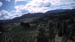 Aerial View: Rural Valley and Farmland with Mountain Vistas In the Sunlight Stock Footage
