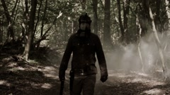 A man in a post-apocalyptic clothes in a black gas mask  goes through the smoke. Stock Footage