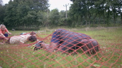 4K Competitors in assault course race crawling under net on the ground Stock Footage