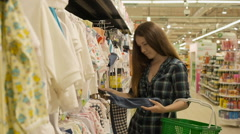 Attractive young mother shopping for childrens clothes in a retail clothing Stock Footage