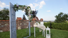 Decorative arch, table and lamp with flowers at a wedding ceremony outdoors Stock Footage