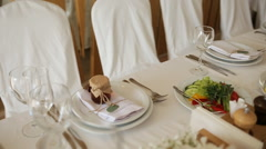 The chairs and table for guests, decorated with candles, served with cutlery and Stock Footage