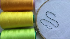 Spools of thread green and wooden hoop with the fabric for embroidery Stock Footage
