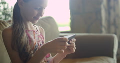Little girl playing games or using app on tablet sitting on white coach in - stock footage