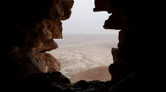 Hole in a rock formation that overlooks the Dead Sea in Masada, Israel Stock Footage