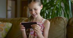 Little girl playing games or using app on tablet sitting on white coach in Stock Footage