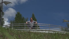 A man walks along the embankment of the city pond. Stock Footage