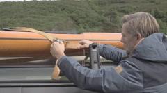 Man tying kayak on car roof Stock Footage