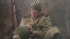 Soviet soldier sits in the trenches, and writes a letter. World War II. Arkistovideo